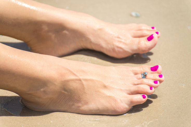 Woman's foot with a ring on a toe and colored nails on the sunny beach