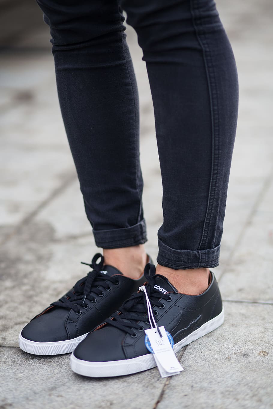 black lacoste sneakers with white soles worn with black skinny jeans